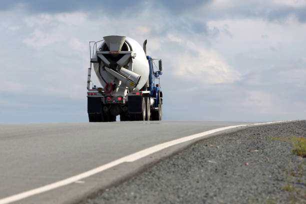 Cement truck alone in road under blue sky stock photo