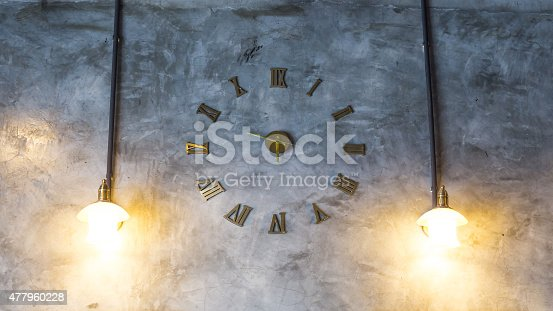 671883446 istock photo Cement wall with vintage clock and light bulbs 477960228