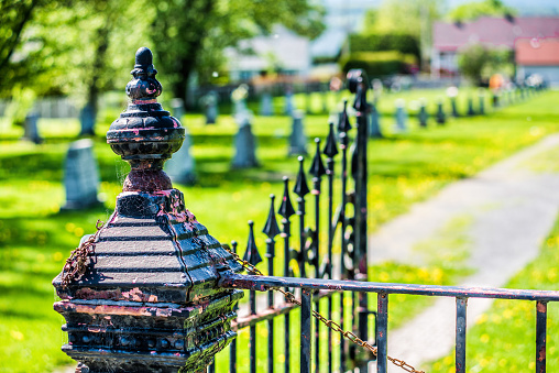 Cemetery and gravestones in summer with vintage metal railing gate fence