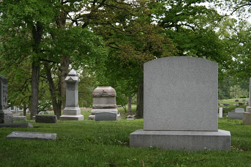 close up on a tombstone ready for your copy.  Other tombstones and dreary cemetary in background.