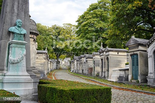Paris, France - October, 2019: Located in the 20th arrondissement, the Père Lachaise Cemetery is the largest necropolis in Paris and one of the most visited in the world with many famous people buried there. Designed in the English garden style, it's a maze of twisting paths under a canopy of beautiful shade trees.
