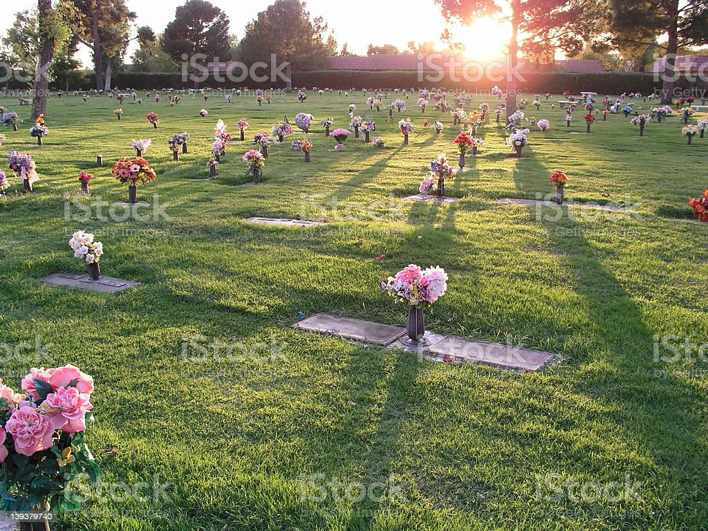 A cemetery with flowers at sunset stock photo