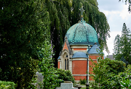 Cemetery with the chapel behind the graves in front of a big willow tree