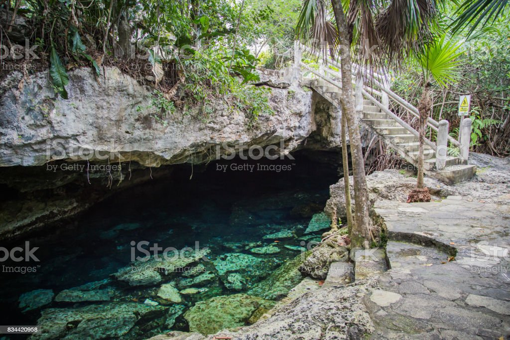 Cenote - natural lagoon with transparent turquoise water surrounded by rocks and tropical vegetation. stock photo