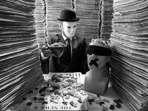 Black and white photo of mid adult man sitting on desk in low key lighting and reading newspaper. Large amount of newspapers are stacked on desk and on the background. He is wearing a black suit, necktie and a bowler hat. His face is obscured with a white mask. A plastic blindfolded mannequin is seen on desk. He is holding a funnel full of letters to fill mannequin brain. The photo was shot with medium format DSLR camera and a wide angle lens in studio lighting.