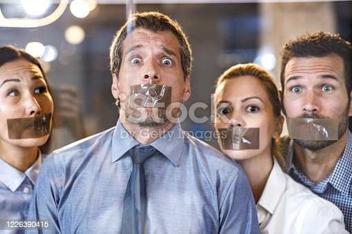 Group of business people with duct tapes on their mouth in the office. Focus is on man looking at camera. The view is through glass.