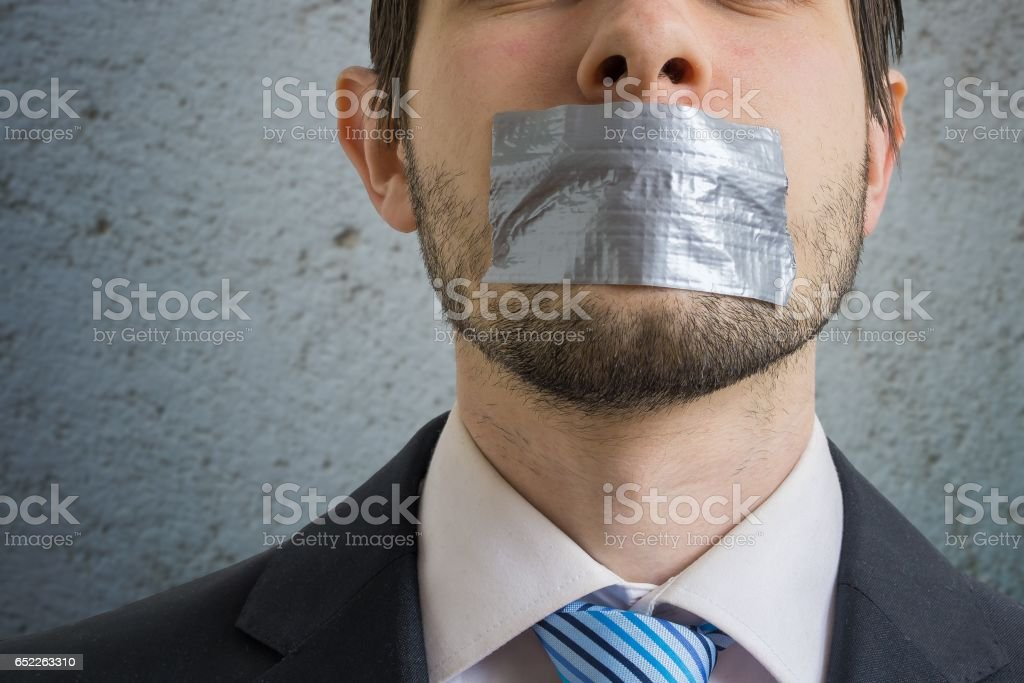 Censorship concept. Man is silenced with adhesive tape on his mouth. stock photo