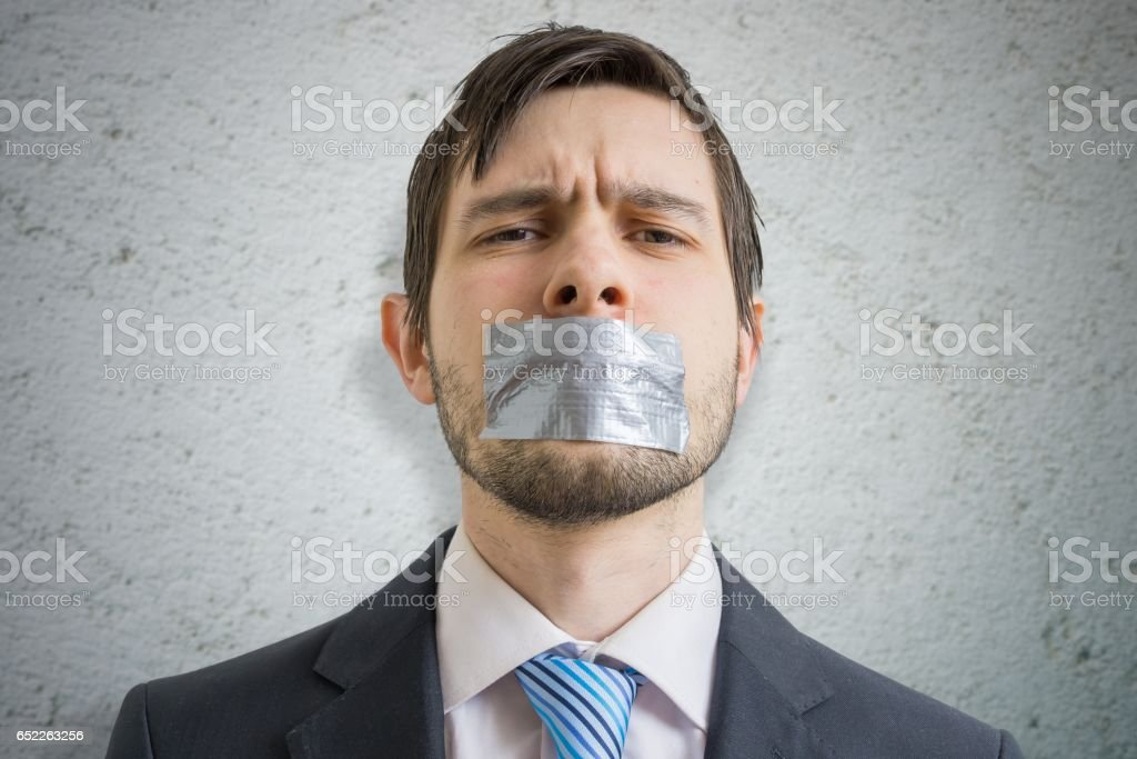 Censorship concept. Young man is silenced with duct tape over his mouth. stock photo