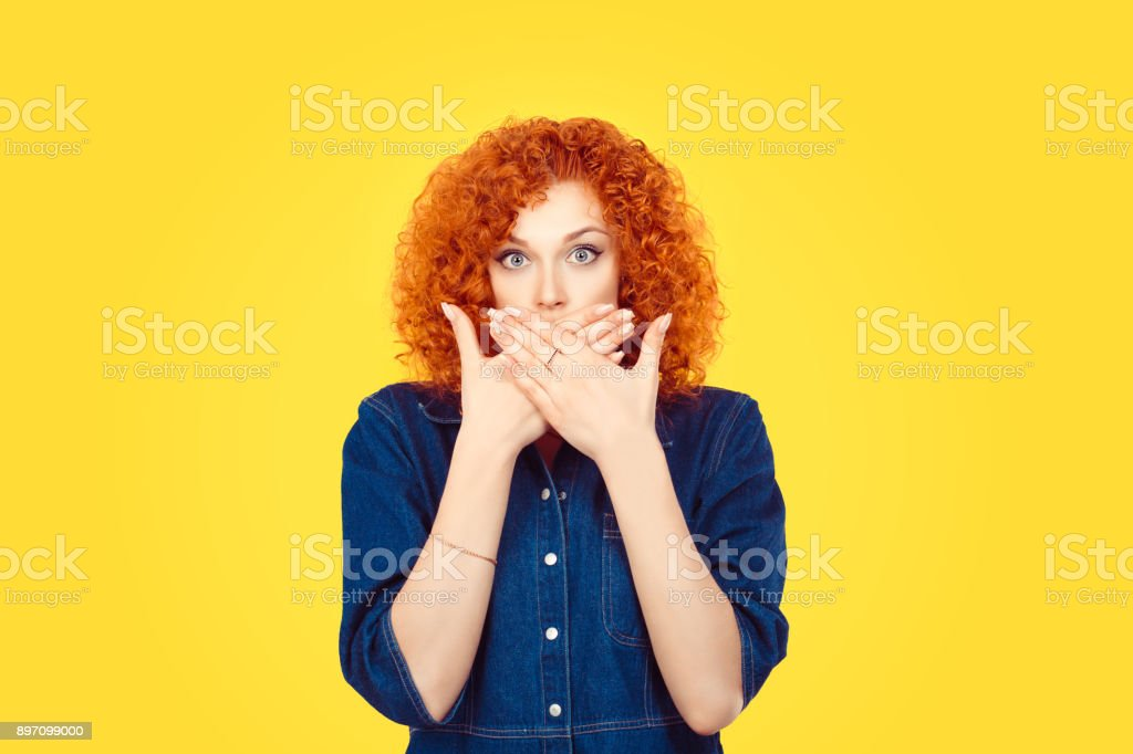 Censorship. Speak no evil concept. Concerned scared redhead woman curly afro hair covering her mouth with hands in blue jeans shirt isolated on yellow background stock photo