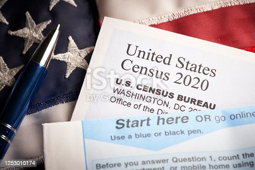Census 2020: survey questionnaire form on desk with American flag.