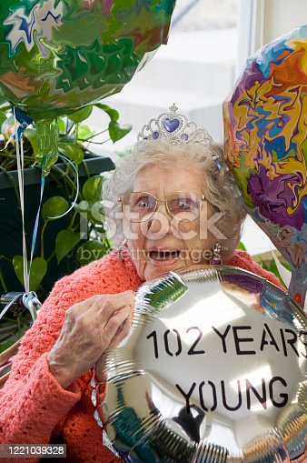 Real life photos of centenarian woman celebrating her birthday of 100+ years. She is happy and holding a balloon that says