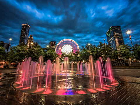 Long exposure of the water fountains in Centennial Olympic Park in Downtown Atlanta, Georgia with the city skyline and Ferris wheel in the background