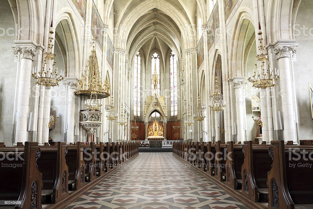 Center aisle of church with pews and arched white pillars stock photo