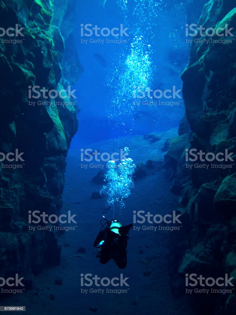 Centered Diver Inside of Continental Split at Silfra in Deep Section at Pingvellir National Park with Bubbles stock photo