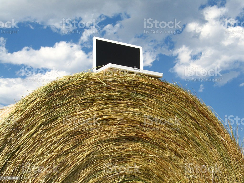Centered Laptop Computer on Large Round Hay-Bale Under Dramatic Sky royalty-free stock photo