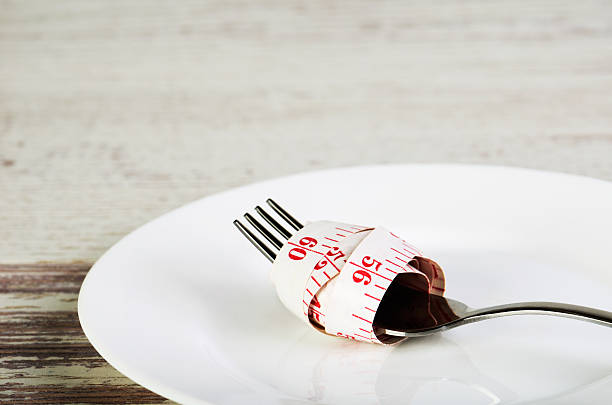centimeter reeled on  fork in  white plate on  wooden table – Foto