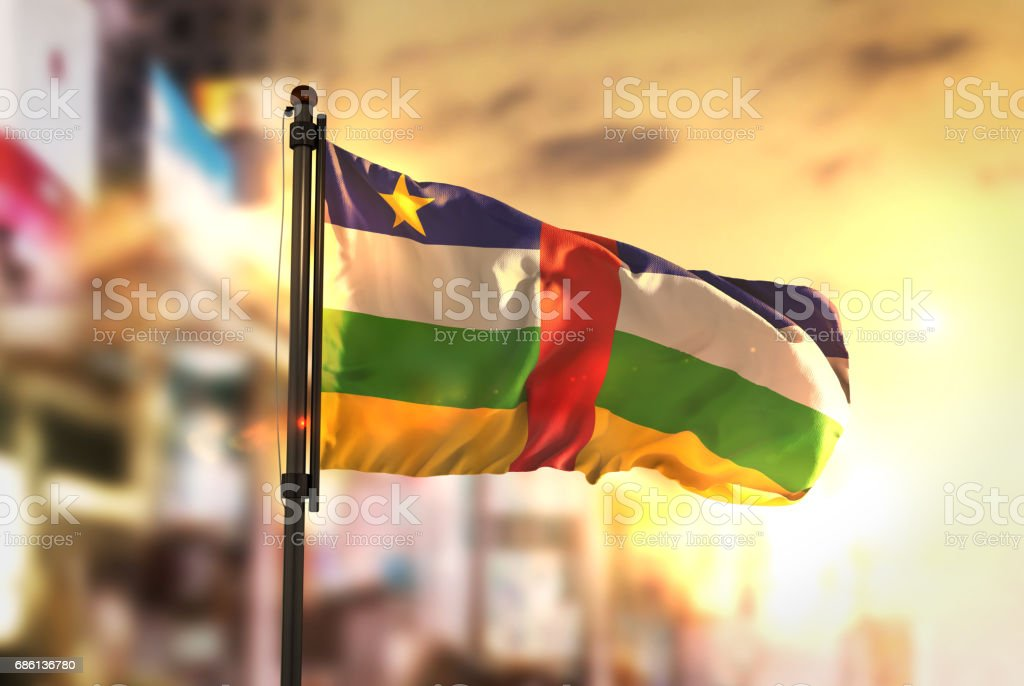Central African Republic Flag Against City Blurred Background At Sunrise Backlight stock photo