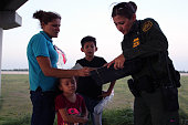 August 16, 2017 - McAllen, Texas, USA - A Border Patrol agent takes a young Honduran woman and her two children who had just crossed the Rio Grande River seeking asylum into custody.  A steady stream of Central Americans, ranging from single children to entire families fleeing gang violence, continue to make the dangerous journey across Mexico to the U.S.