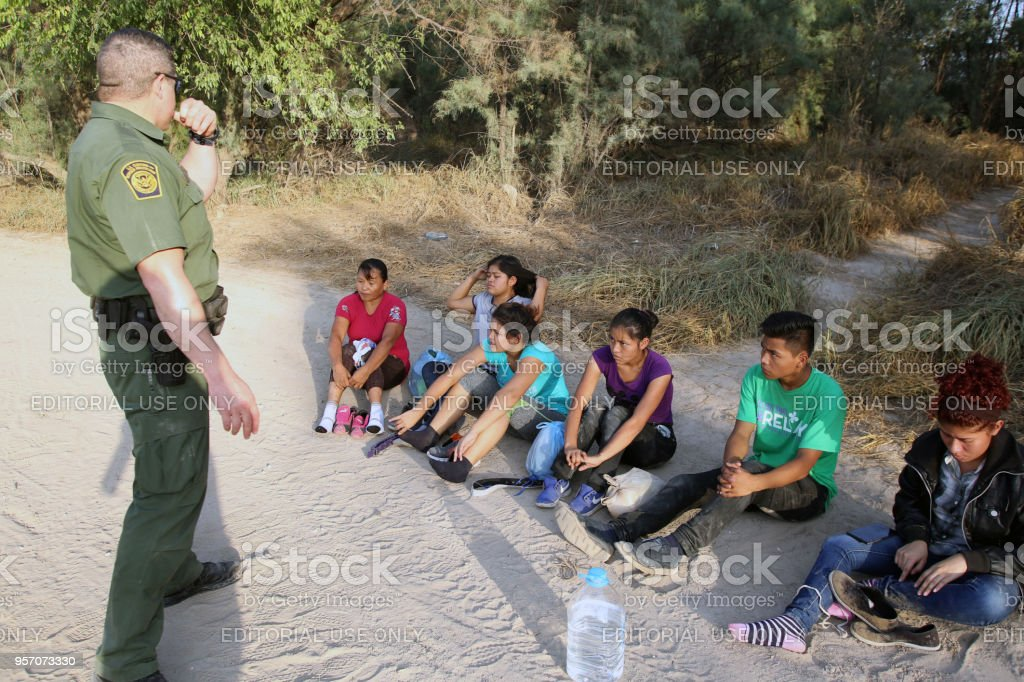 Central American Refugees, South Texas McAllen, Texas, USA - August 16, 2017: A small group of Central American refugees turn themselves in to the Border Patrol after illegally entering the United States by crossing the Rio Grande River in deep south Texas.  A steady stream of Central Americans, ranging from single children to entire families fleeing gang violence, continue to make the dangerous journey across Mexico to the U.S. Adult Stock Photo