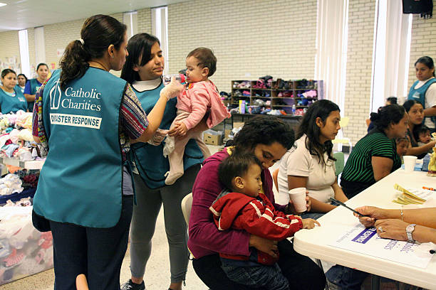Central American Refugees, South Texas, Summer 2014 McAllen, TX, USA - July 8, 2014: Two volunteers with a Catholic Charities Disaster Relief Team give a Central American refugee baby a bottle containing pedialyte, while a mother offers her young son a cup of water at the reception hall of Sacred Heart Catholic Church where they will receive counselling, food, clothes and a shower before boarding a bus for the homes of relatives in the U.S. Virtually all of the refugees arrived de-hydrated.  border patrol stock pictures, royalty-free photos & images