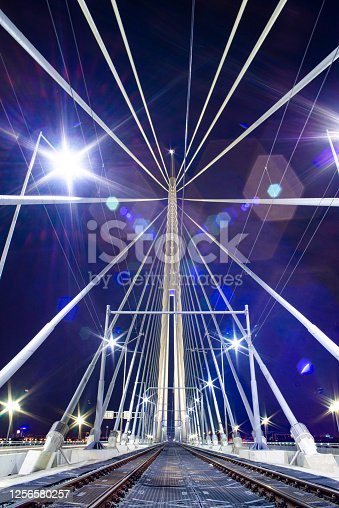 Nighttime photo of a central bridge pylon with it's cables stretching from it in all directions.