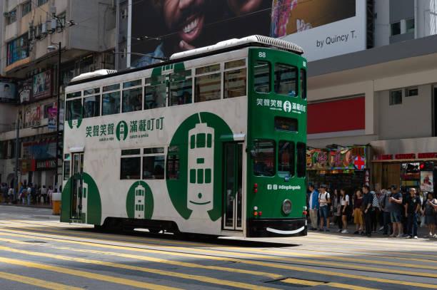 central, hong kong - circa april,2018:  double deck tram on busy street of central hong kong. - linea tranviaria foto e immagini stock