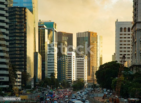 Central Jakarta Sudirman area financial district skyline at sunset,  featuring the rapidly growing downtown area rising above highways.