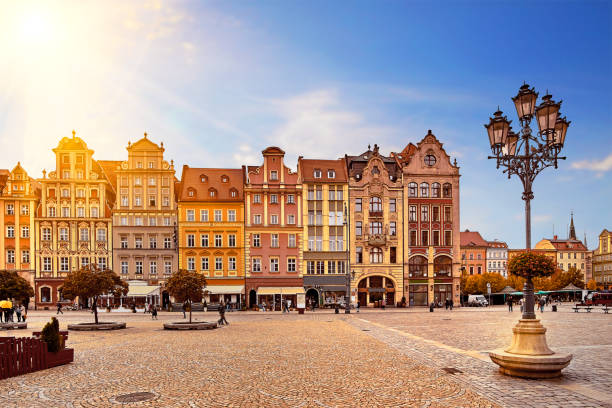 central market square in wroclaw poland with old colourful houses, street lantern lamp and walking tourists people at gorgeous stunning morning sunrise sunshine. travel vacation concept - poland stock photos and pictures