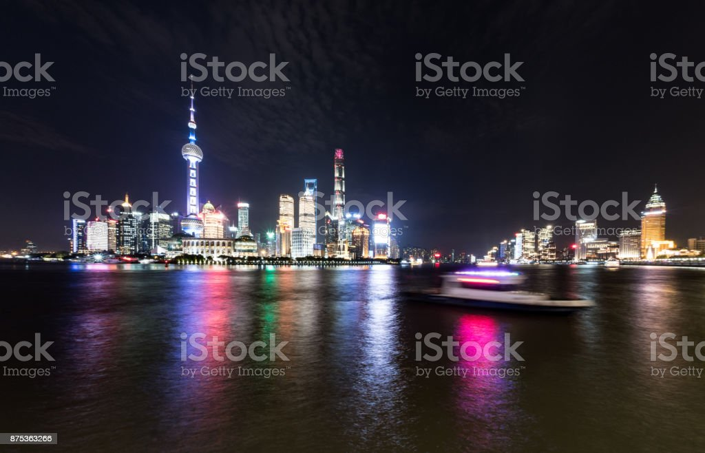 Central Shanghai Skyline at night with blurred motion boats stock photo
