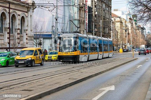 Sofia, Bulgaria - February 28, 2021: A tram passes in front of Halite. Covered market in the center of Sofia, the capital of Bulgaria, located on Maria Luiz Boulevard. It was opened in 1911