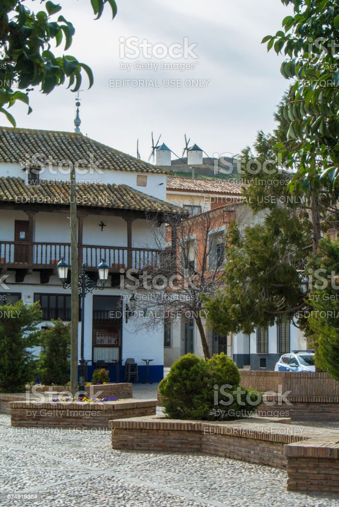 A central square of Consuegra town and a view of the hill with old white traditional windmills, Castilla La Mancha, Spain. royalty-free stock photo