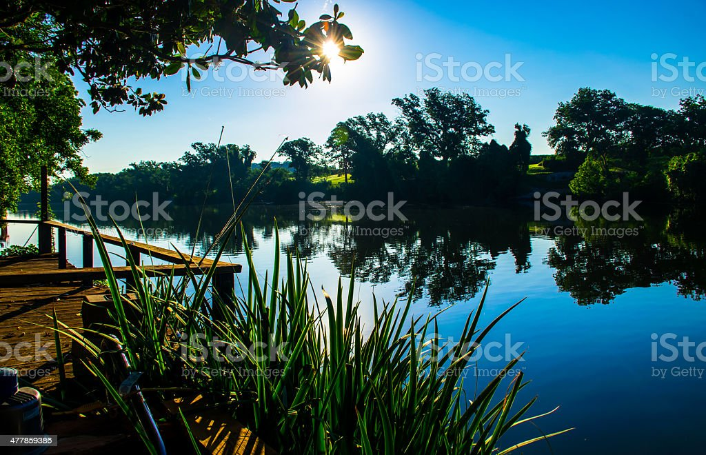 Central Texas Mirror Lake Sun Rays Reeds Water front property stock photo