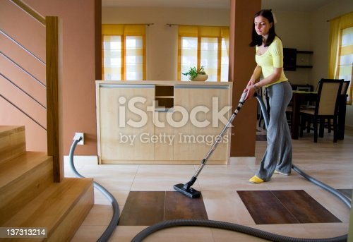 Young woman cleaning floor using a central vacuum system (also known as built-in or ducted vacuum cleaner).