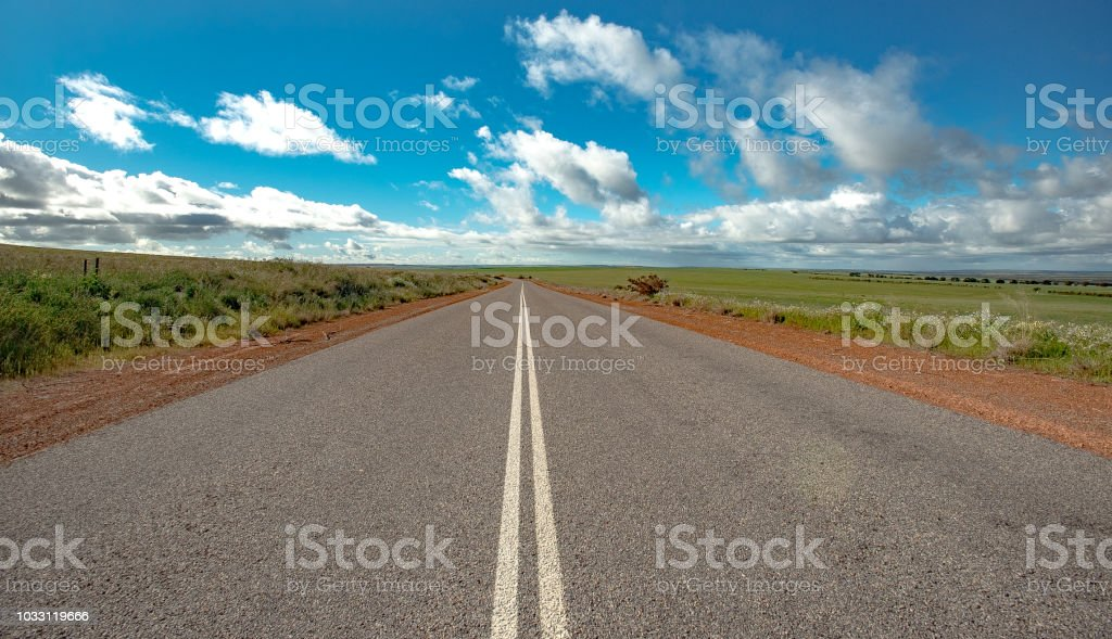 Centre of road photograph looking down the twin white lines to infinity and the sky and cloud horizon in Western Australia stock photo
