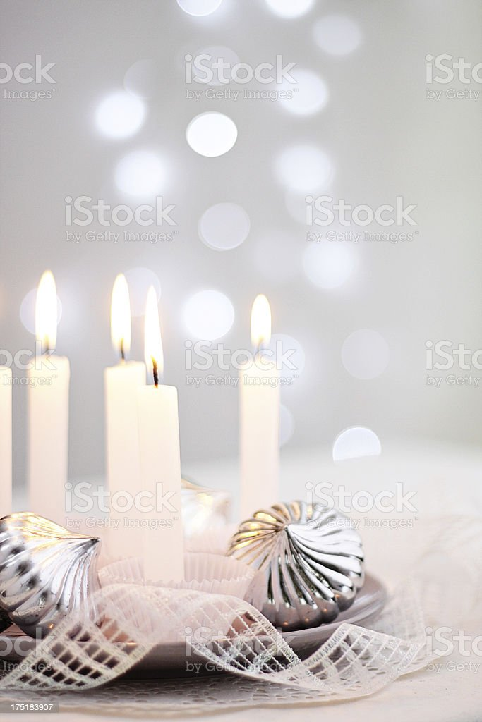 Centrepiece with silver Christmas ornaments, candles and Christmas lights background stock photo