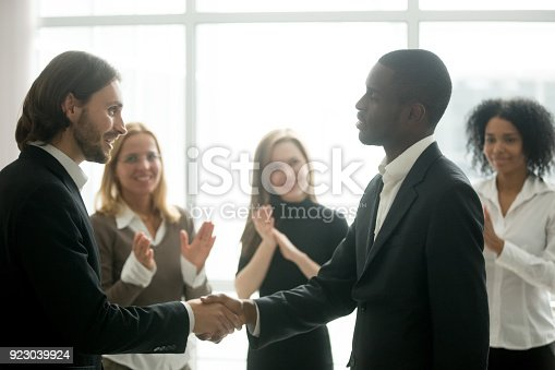 istock Ceo with team appreciating black manager by handshake and applause 923039924