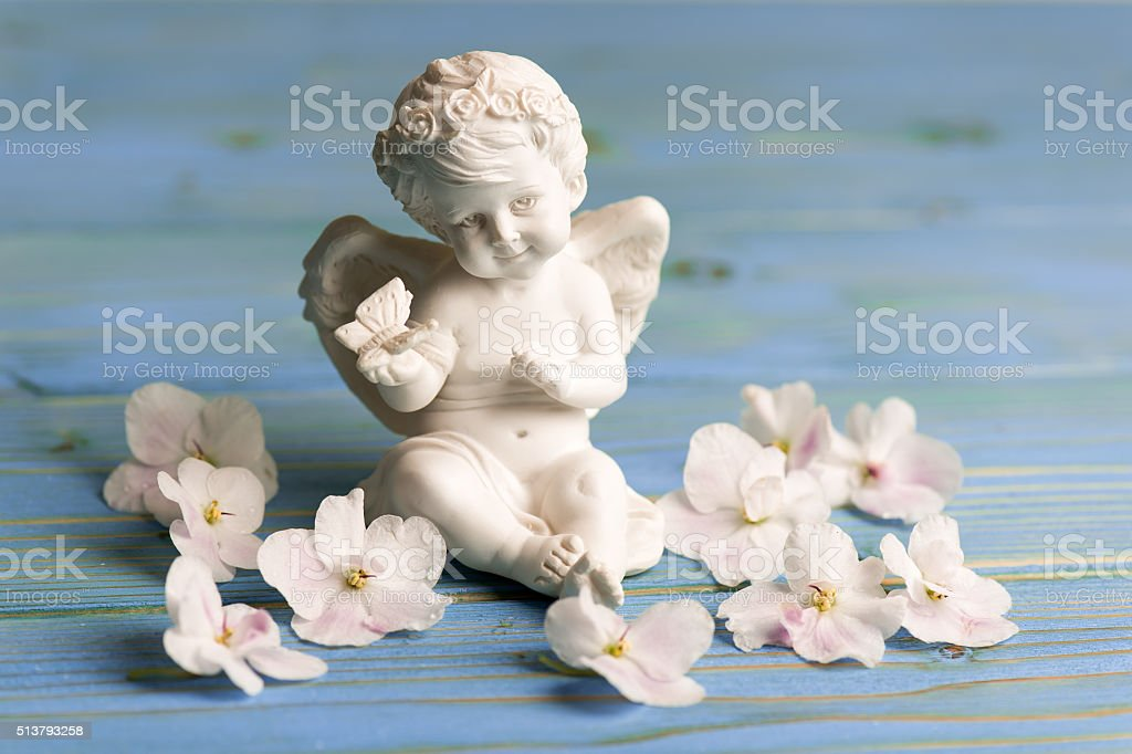 Ceramic angel with saintpolia flowers on the wooden background. stock photo