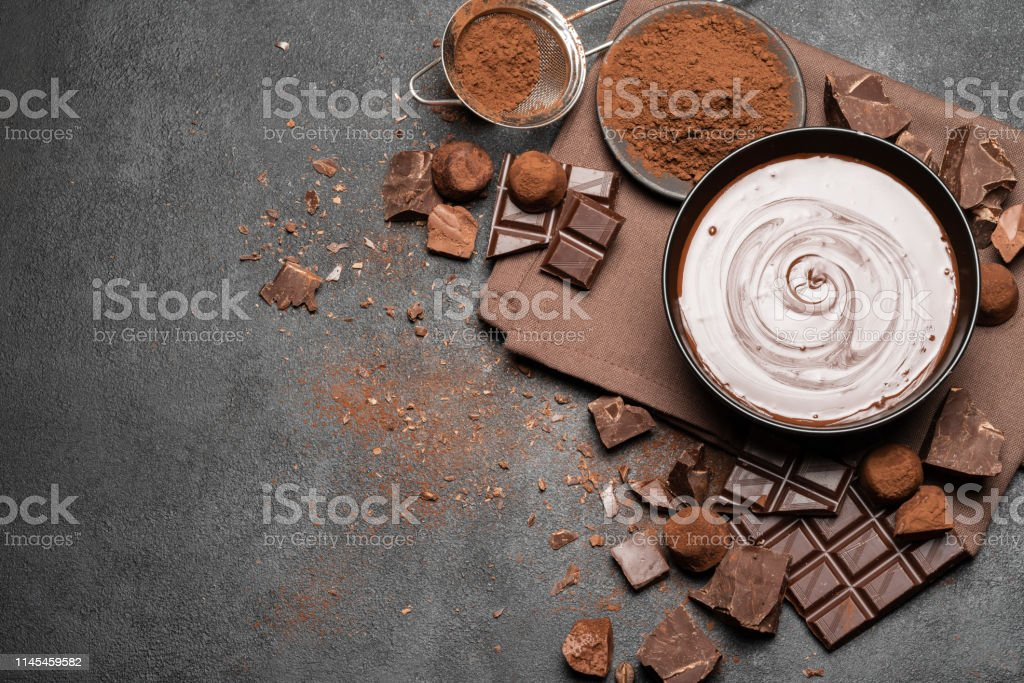ceramic bowl of chocolate cream or melted chocolate and pieces of...
