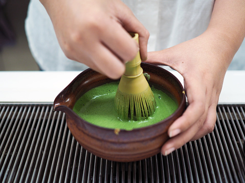 Ceramic bowl of Japanese green tea and bamboo whisk on preparing table.