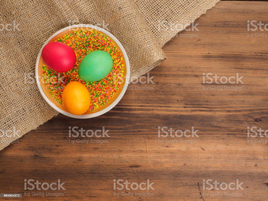 Ceramic bowl with colorful sweet powder and easter colored egg. Russian and Ukrainian, orthodox slavic traditional Easter kulich on rural background. Old wood, red mesh paper and burlap foto stock royalty-free