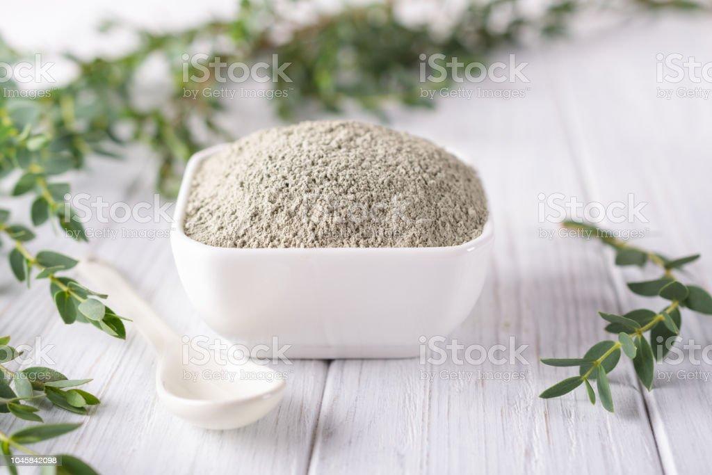 Bol en céramique avec la poudre d'argile verte et d'eucalyptus fraîches feuilles sur fond blanc. Concept de soins visage et corps. - Photo