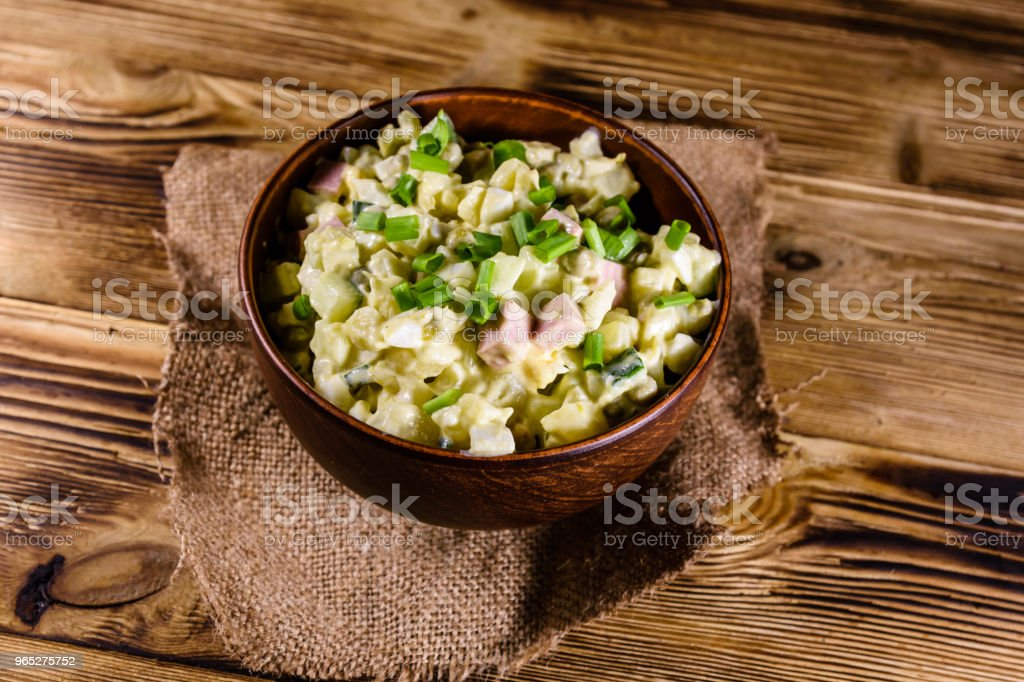 Ceramic bowl with russian traditional salad olivier on wooden table royalty-free stock photo