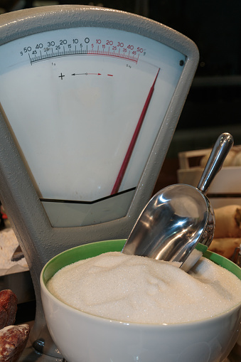 Ceramic Bowl with Sugar on Antique Scale for Aliment in the Shop