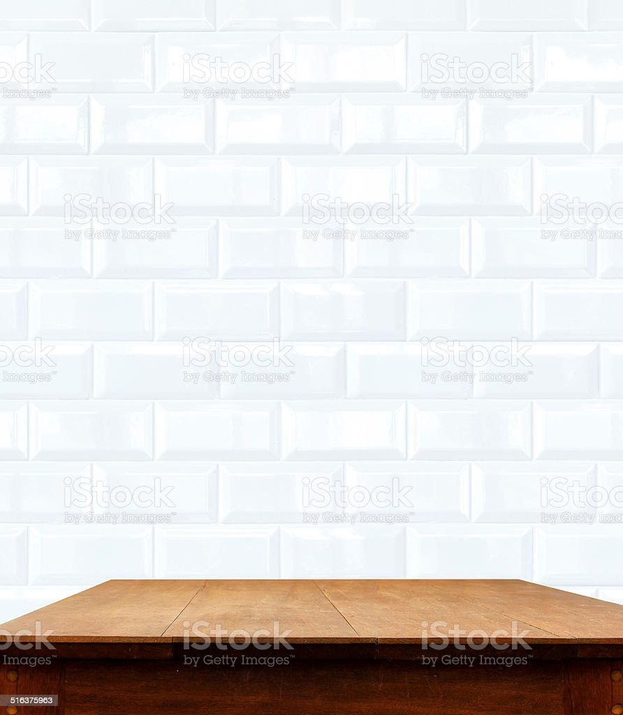 ceramic brick tile wall and wooden table stock photo