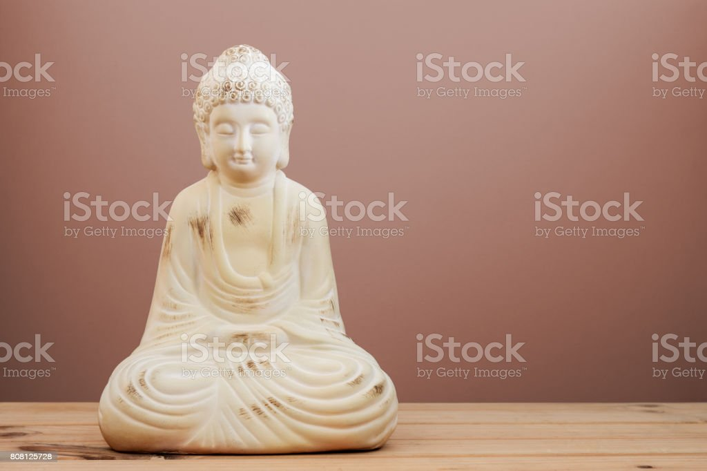 Ceramic Buddha statue with plain background & copy space for text. stock photo