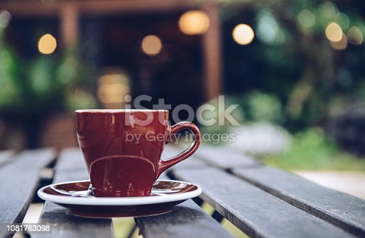 647209792 istock photo A ceramic cup of coffee on the wood plank table with beautiful light bokeh in the background. 1081763098