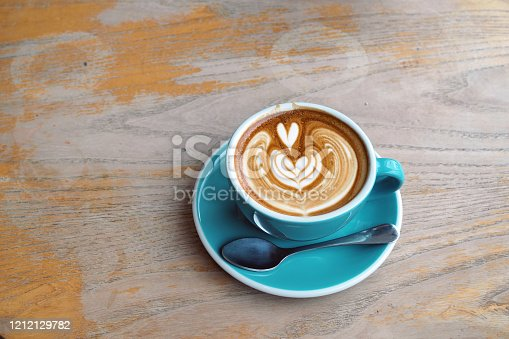 A ceramic cup of hot coffee with beautiful heart shape latte art on wooden table background. Selective focus.