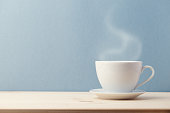 Small white cup on saucer with steam coming from hot delicious drink on blue background.