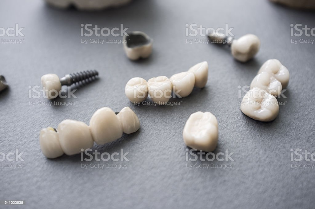 Ceramic dentures and crowns on gray background stock photo