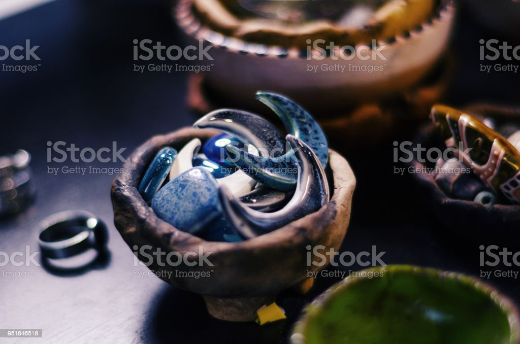 Ceramic details of handmade jewelry in a ceramic bowl on a master table stock photo